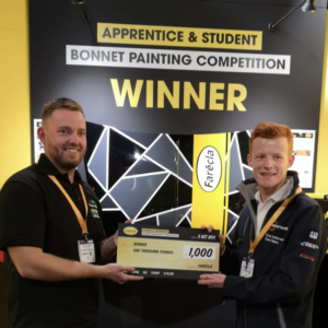 The Figaro Shop's Elliot Campbell (L) receiving prize cheque from Nationwide CRC's Daryl Head (R) in front of Elliot's winning bonnet on the Farécla stand at Advanced Engineering 2018